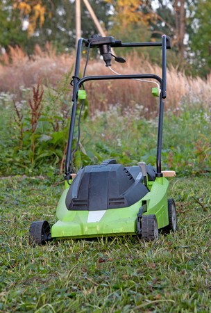 grass plot: modern electric lawn mower on the unmown lawn