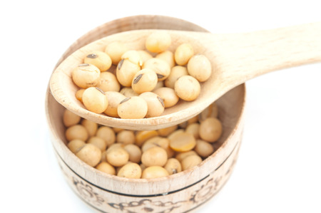 soybeans: soybeans on wooden spoon in a wooden bowl on a white background