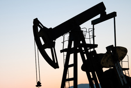 remediation: operating oil and gas well profiled on sunset sky
