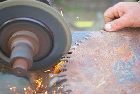 sharpening saw by abrasive disk machine Stock Photo