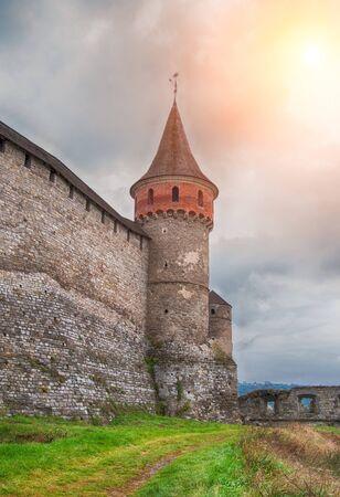 sunset over the tower of medieval half-ruined castle in Kamenetz-Podolsk, Ukraine
