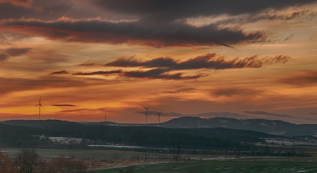 erzgebirge: winter landscape during the sunrise with fog and a windmill