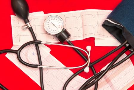 medical manometer lying on cardiogram chart closeup. Stock Photo