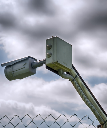 barbed wire fence: barbed wire and surveillance camera