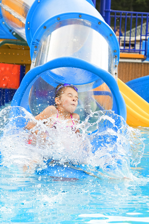 girl has into pool after going down water slide during summer