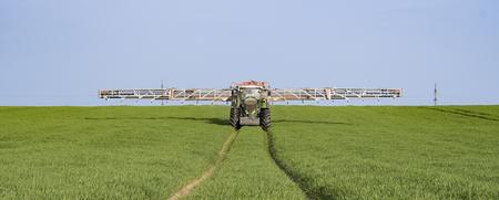 Tractor spraying wheat field with sprayer Standard-Bild - 120312703