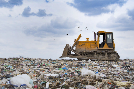 bulldozer working on landfill with birds in the sky Stock fotó