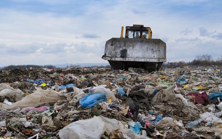 Bulldozer working on mountain of garbage in landfill