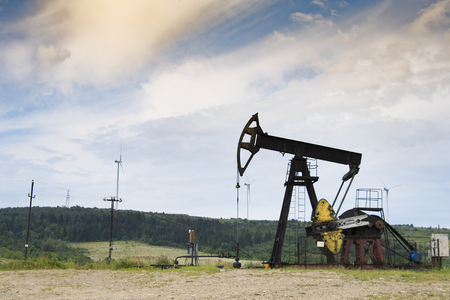 Oil and gas industry. Work of oil pump jack on a oil field. White clouds and blue sky Reklamní fotografie