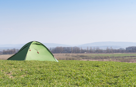 Tourist tent. Camping on the grass in sun