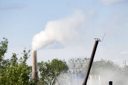 smoke, air emissions from an industrial pipe against green trees. Pollution of the environmen.