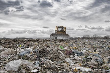 bulldozer working on landfill with birds in the sky. Sunset Stock Photo