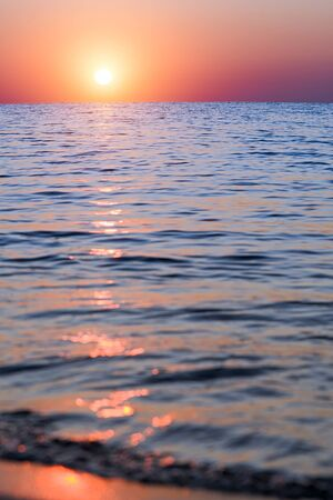 Bright sunset with large yellow sun under the sea surface Stock Photo