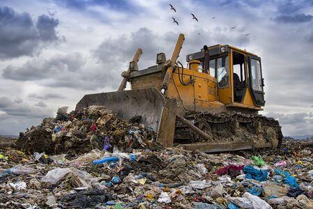 bulldozer travaillant sur une décharge avec des oiseaux dans le ciel