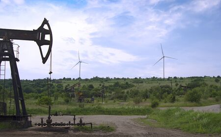 Operating oil and gas well, profiled on blue sky with clouds and wind turbine