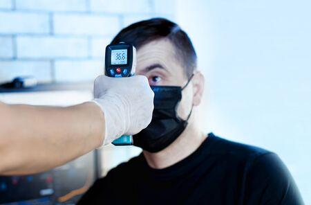 doctor measures the temperature of a man for coronavirus symptoms.
