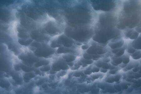 Menacing mammatus clouds before the storm, stormy sky, climate change and unpredictable terrifying mother nature Stock Photo
