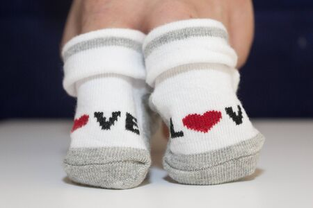hands holding small baby socks.