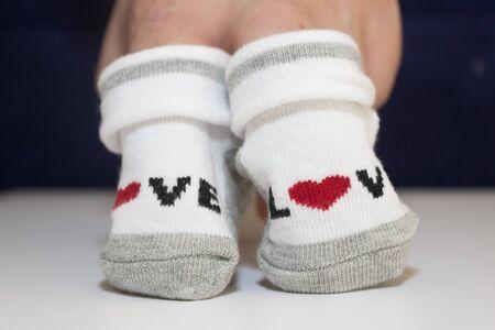 manos sosteniendo pequeños calcetines de bebé.