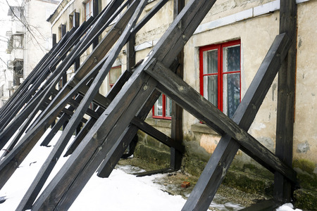 Wooden boards supporting old building from ruining. Concept of long-term support relationship