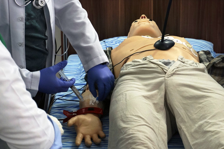 Medical simulation procedure. Medical student as a doctor performing iv injection to a mannequin dummy as a simulated patient.