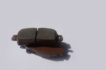 New auto brake pads on grey background