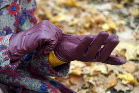 Mains féminines portant des gants en cuir marron rouge sur fond de feuilles jaunes.