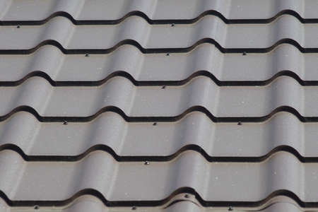 Metal tile roof of gray color.