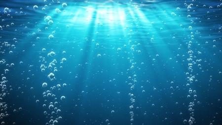 fondali marini: Onde del mare blu dal subacquea con i raggi bolle luce che brilla attraverso Grande per gli sfondi