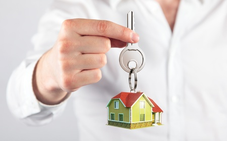 keychain: giving house key with a keychain house model form Stock Photo