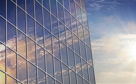 Una reflexión nubes en la pared de vidrio del edificio