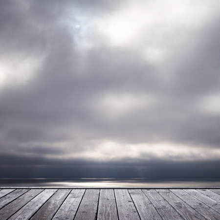 somber: wood floor and somber sky and see
