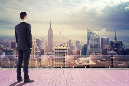 businessman standing on pier and looking at city photo