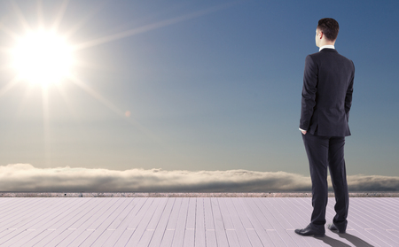 businessman standing on pier and looking at sun Stock Photo