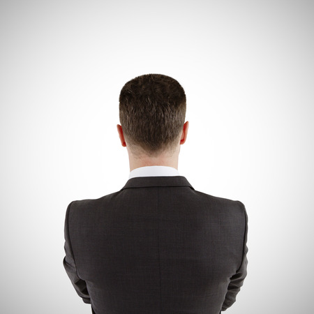 head back: businessman in suit stands with his back on a white background