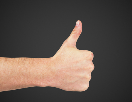 hand with thumb up isolated on black photo
