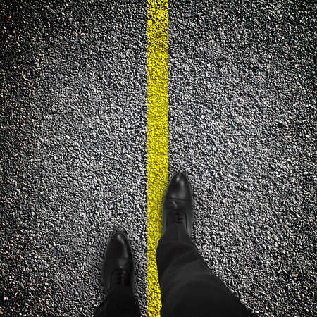 feet are on the road with a yellow stripe Imagens