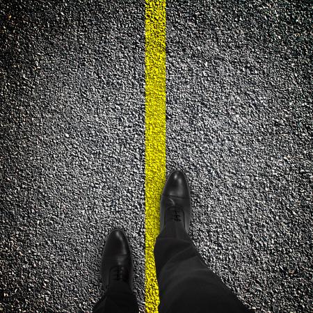 voeten op de weg met een gele streep Stockfoto