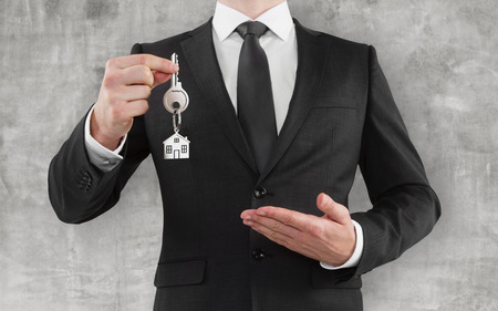 trinket: businessman in suit gives a key with trinket Stock Photo