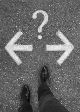 pair of feet standing on tarmac road with  arrows and question mark