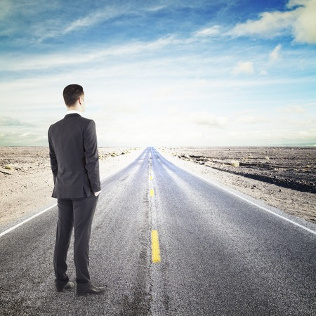 young businessman standing on road looking to horizont photo