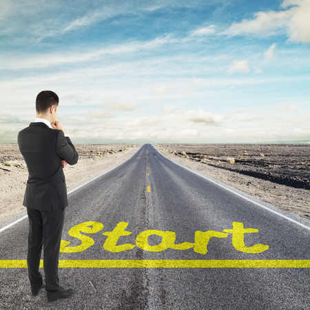 commence: businessman looking to horizont before yellow start line Stock Photo