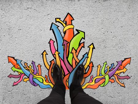 paar voeten staan op een geasfalteerde weg met kleur pijlen Stockfoto