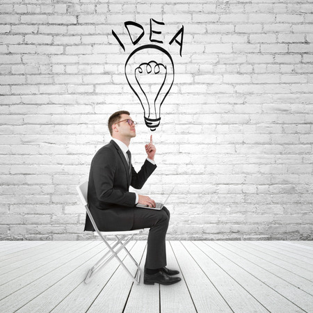 businessman sitting in brick room with notebook and pointing to lamp photo