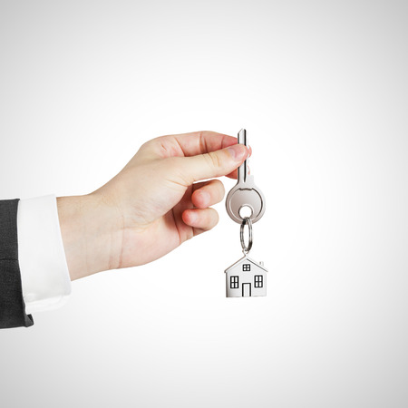 house key: hand with key with trinket on white background Stock Photo