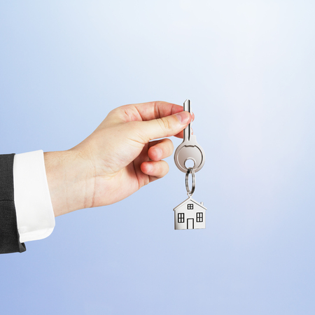 passkey: hand and key with trinket on blue background