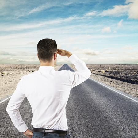 businessman standing on road looking to horizon photo