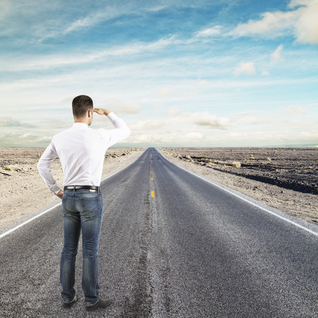 man standing on road looking to horizon photo