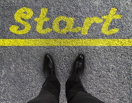 paar voeten op een geasfalteerde weg met gele druk van woord start