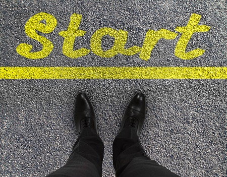 commence: pair of feet on a tarmac road with yellow print of word start